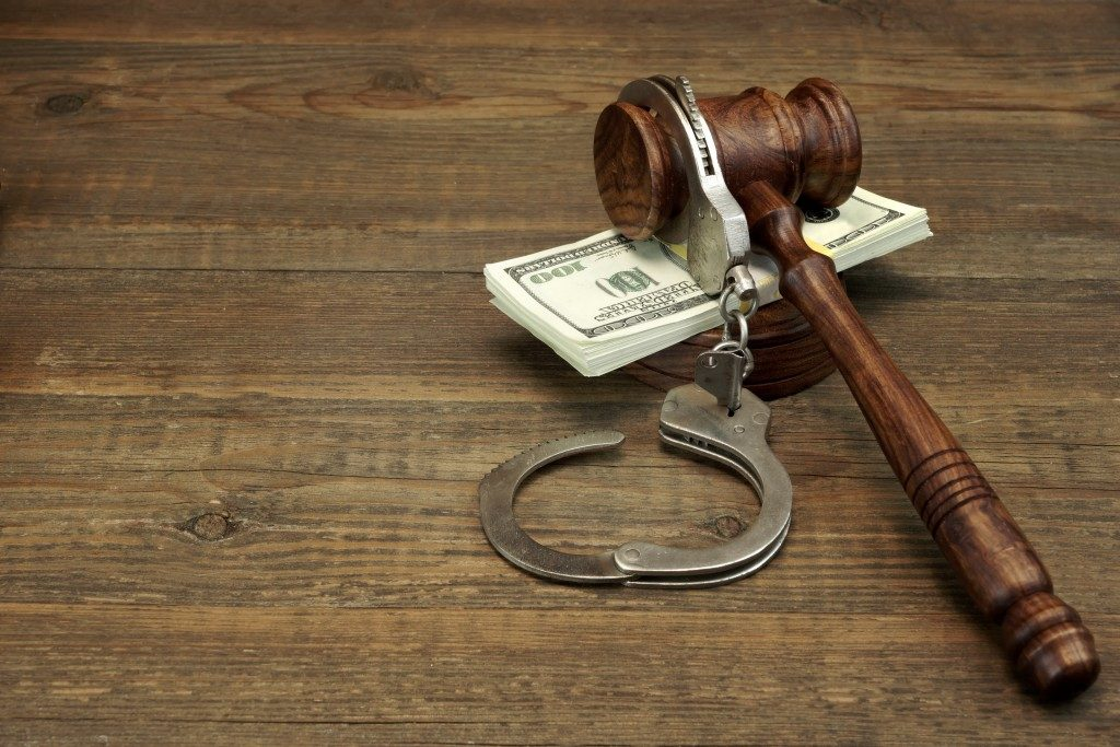 Cash, Real Handcuffs And Judge Gavel On Rough Wood Background