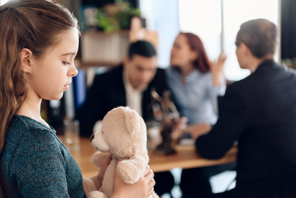 Child looking at stuffed toy while parents argue