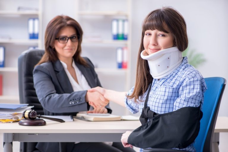 woman with neck brace consulting lawyer