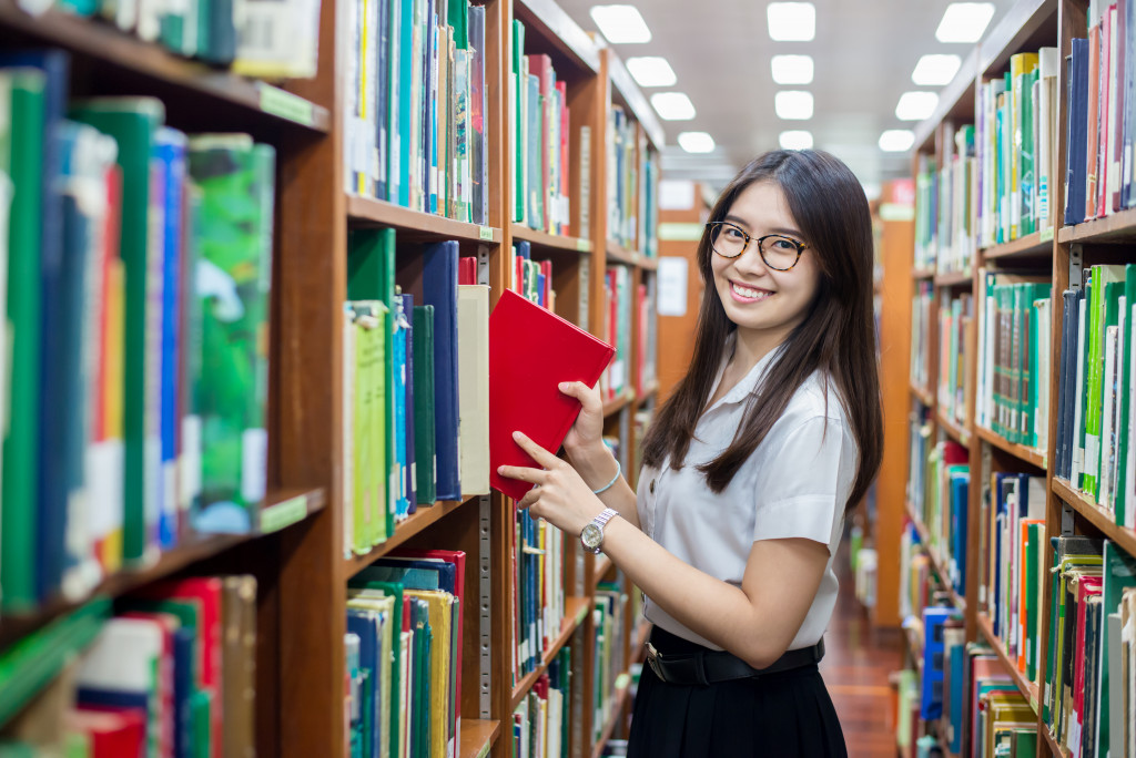 woman getting a book from the shelf